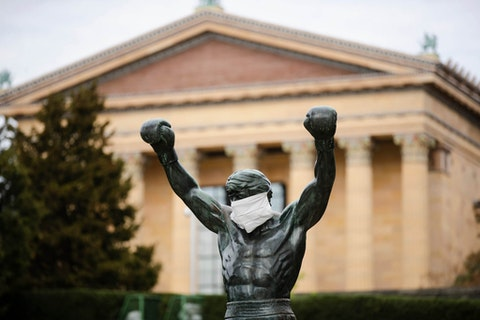 In this April 14, 2020, file photo the Rocky statue is outfitted with a mock surgical face mask at the Philadelphia Art Museum in Philadelphia. Philadelphia is banning indoor dining at restaurants and plans to shutter gyms, museums and libraries as the city battles a resurgence of the coronavirus, officials announced Monday, Nov. 16, 2020. (AP Photo/Matt Rourke, File)