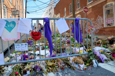 CHARLOTTESVILLE, VA - August 2017: Memorial flowers and notes are left at the spot where Heather Heyer was killed and others were injured when a car plowed into a crowd of protesters during a rally. (Image via Shutterstock)