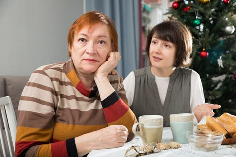 A red-haired, middle aged woman gazes off in the distance while her brunette companion urgently shares divergent political views.