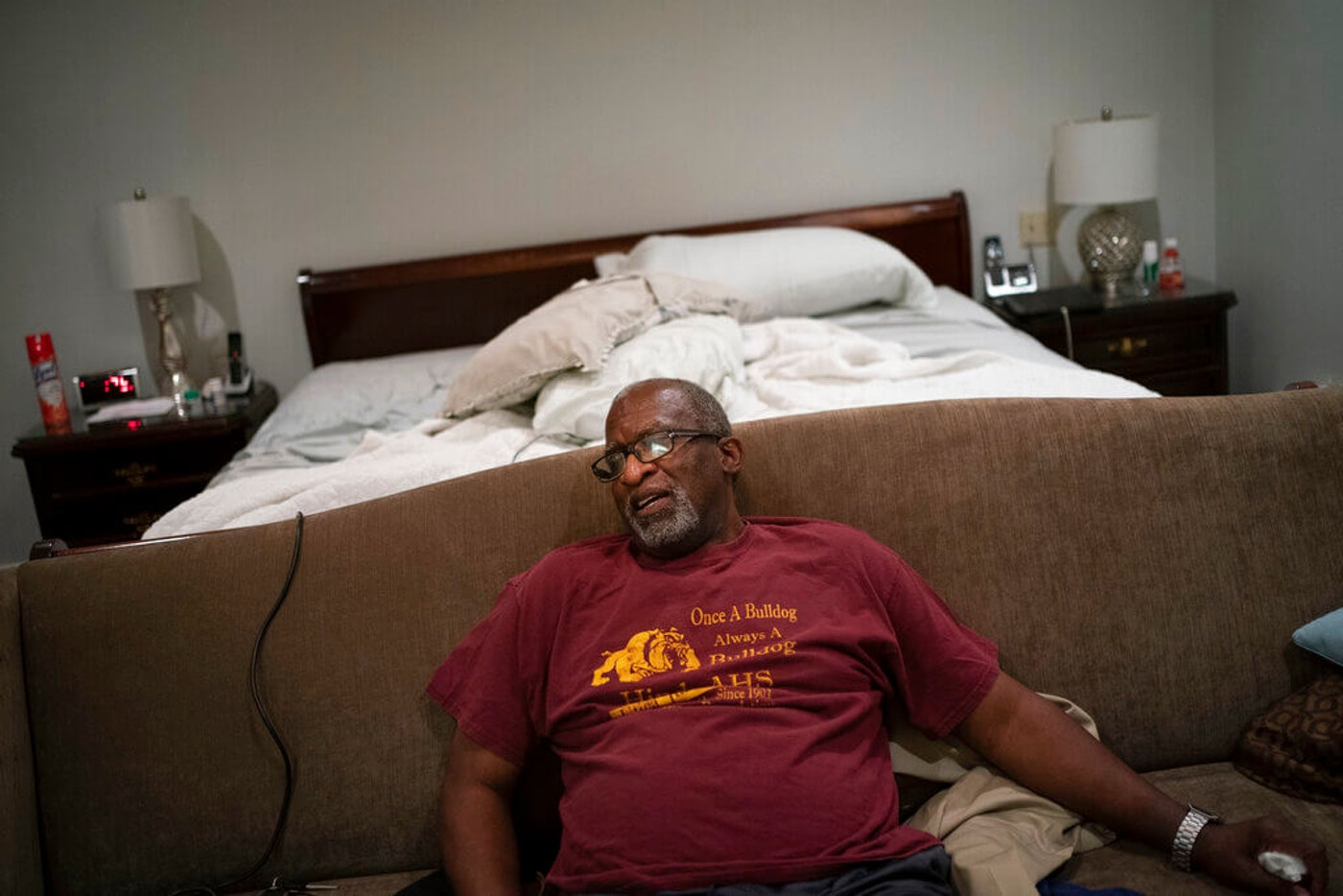 a man sitting in his bedroom sick with COVID-19 with no family around to help