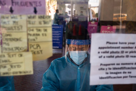 healthcare worker at a testing site as COVID-19 death tolls rise