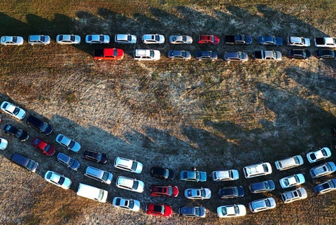 In this aerial view from a drone, people line up in their cars to receive food assistance at the Share Your Christmas food distribution event sponsored by the Second Harvest Food Bank of Central Florida, Faith Neighborhood Center, and WESH 2 at Hope International Church on December 9, 2020 in Groveland, Florida, near Orlando. As government support has run out and food banks are strapped, more Americans are shoplifting to make ends meet. (Photo by Paul Hennessy/NurPhoto via Getty Images)