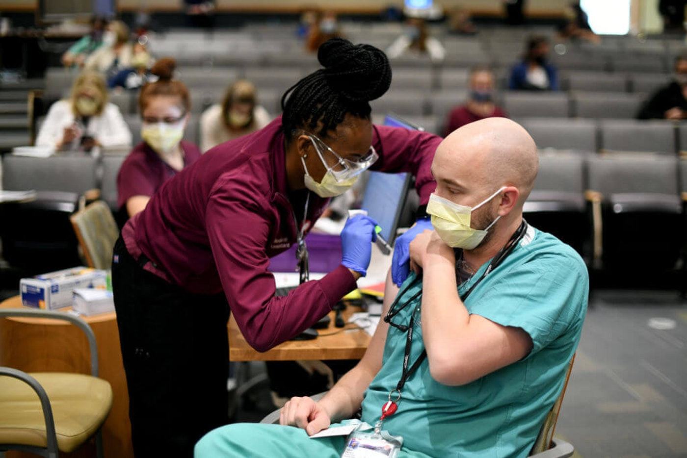 Medical assistant Shalice Wheeler, left, administers COVID-19 vaccine to physician assistant Matt Ferraro at UCHealth University of Colorado Hospital in Aurora, Colorado, on Thursday. Dec. 17, 2020. (The Denver Post Photo via Getty Images/Hyoung Chang)