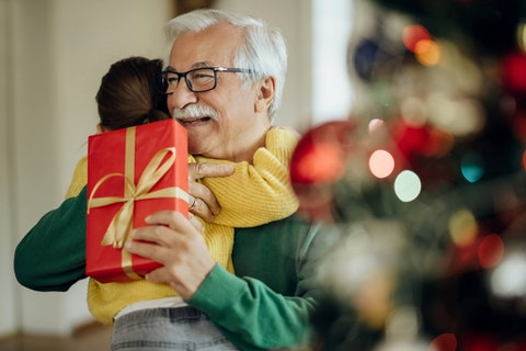 A grandfather gets a gift from his granddaughter. (Shutterstock Photo/Drazen Zigic)