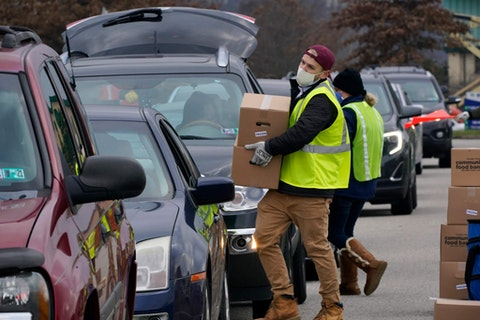 Volunteers load boxes of food into a car during a Greater Pittsburgh Community Food bank drive-up food distribution in Duquesne, Allegheny County, on Nov. 23, 2020. (AP Photo/Gene J. Puskar)
