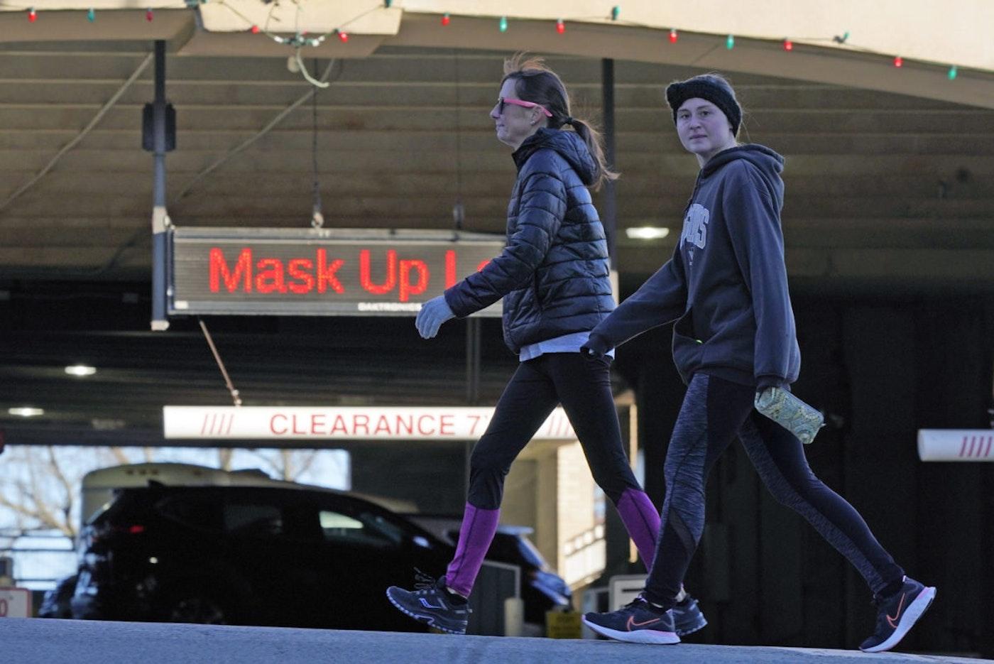 Two women walk past a sign on a parking garage in Mount Lebanon, Pa., reminding people to wear masks, Nov. 18, 2020. (AP Photo/Gene J. Puskar)