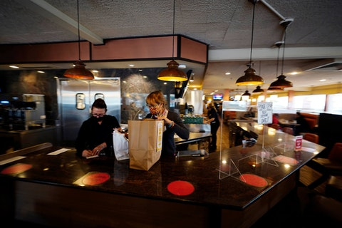 Managers Yllka Murati, left, and Cynthia Branche organize takeout orders at the Penrose Diner, Tuesday, Nov. 17, 2020, in South Philadelphia, just before the city ordered a halt to indoor dining. (AP Photo/Matt Slocum)