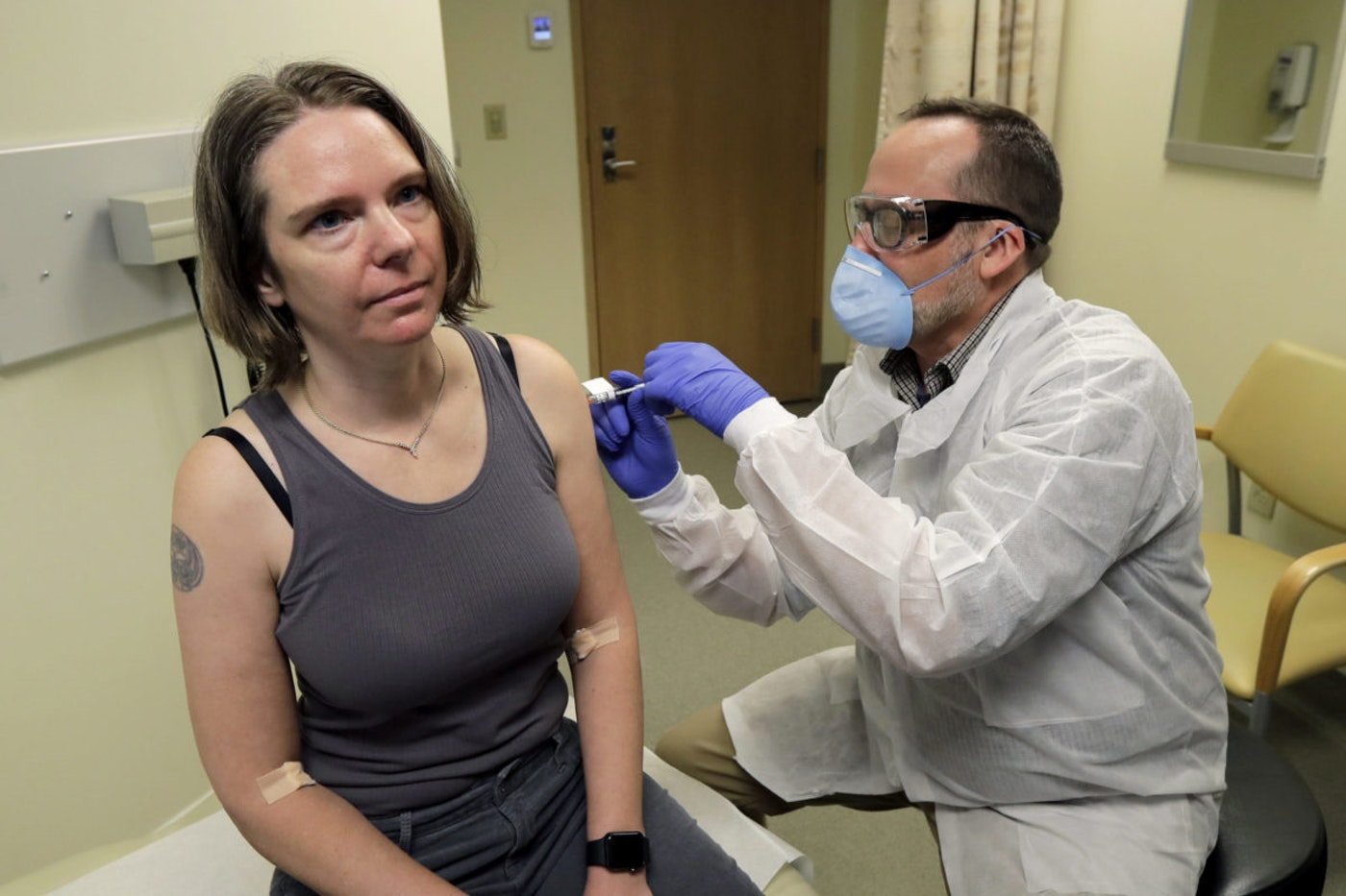 In this March 16, 2020 file photo, a pharmacist gives Jennifer Haller, left, the first shot in the first-stage safety study clinical trial of a potential vaccine for COVID-19, the disease caused by the new coronavirus, at the Kaiser Permanente Washington Health Research Institute in Seattle. The world's biggest COVID-19 vaccine test got underway July 27 with the first of 30,000 planned volunteers. (AP Photo/Ted S. Warren, File)