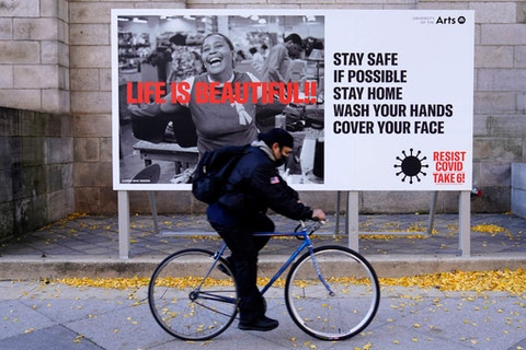 A man wearing a face mask bicycles along Broad Street, Wednesday, Nov. 18, 2020, in Philadelphia. Pennsylvania is strengthening its mask mandate and will require out-of-state travelers to test negative for the coronavirus before arrival, health officials announced Tuesday, taking additional steps to address a sharp increase in infections and hospitalizations. (AP Photo/Matt Slocum)