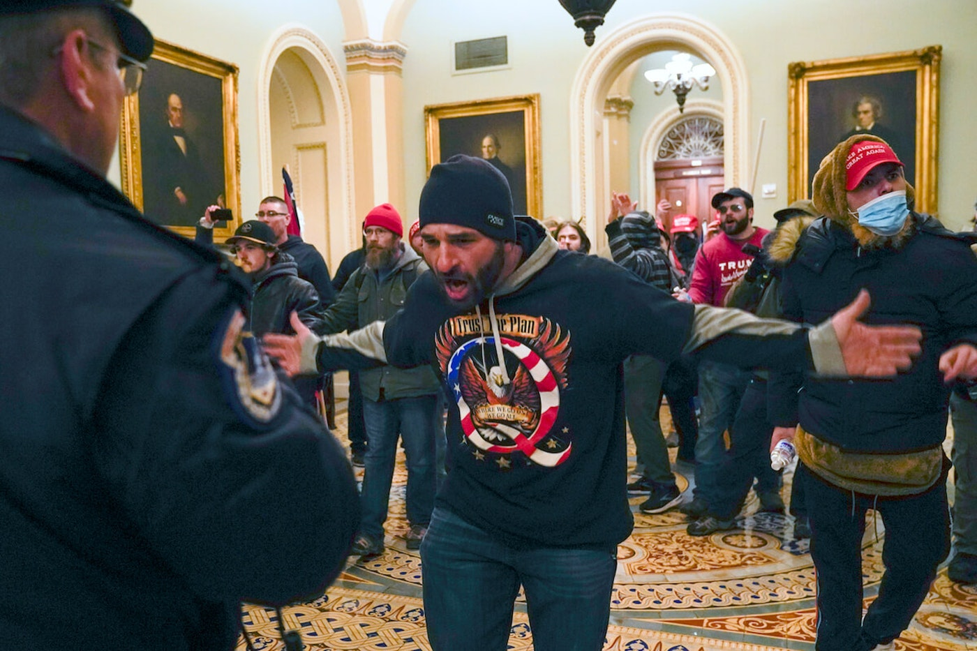 Domestic terrorists gesture to US Capitol Police in the hallway outside of the Senate chamber at the Capitol in Washington, Wednesday, Jan. 6, 2021. (AP Photo/Manuel Balce Ceneta)