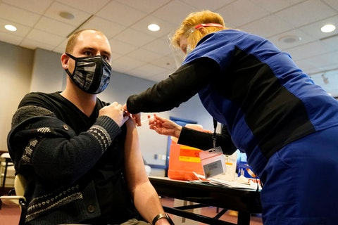 Penny Cracas, right, with the Chester County, Pa., Health Department, administers the Moderna COVID-19 vaccine to Robert Dando, a school district nurse, at the Chester County Government Services Center, Tuesday, Dec. 29, 2020, in West Chester. (AP Photo/Matt Slocum)