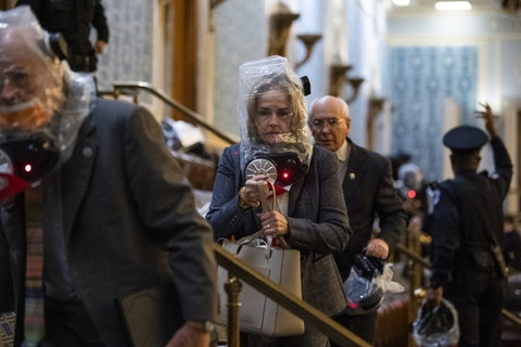 Rep. Madeleine Dean, D-Pennsylvania, and other members take cover as protesters disrupt the joint session of Congress to certify the Electoral College vote on Wednesday, Jan. 6, 2021. (CQ-Roll Call Photo via Getty Images/Tom Williams)