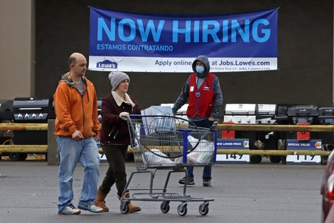 A Lowe's employee walks through the parking lot as shoppers walk to their car after shopping at a store in Robinson Township, Allegheny County, on Wednesday, May 6, 2020. (AP Photo/Gene J. Puskar)