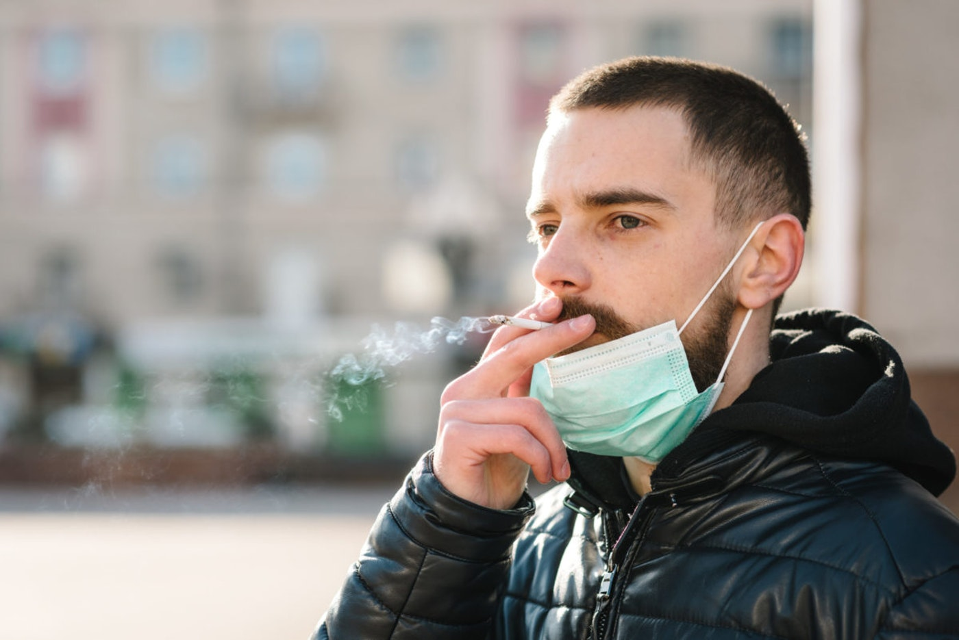 An unidentified man smokes a cigarette during the coronavirus pandemic. (Shutterstock Photo/Sergii Sobolevskyi)