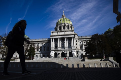 FILE- In this file photo from Nov. 19, 2019, a man is silhouetted in the shade as he walks by the Pennsylvania Capitol in Harrisburg, Pa. There are 203 House seats and 25 of 50 Senate seats up for election on Nov. 3, when voters will decide whether to extend gains Democrats made two years ago or tighten the majority hold Republicans have long held over both chambers of the Pennsylvania Legislature. (AP Photo/Matt Rourke, File)