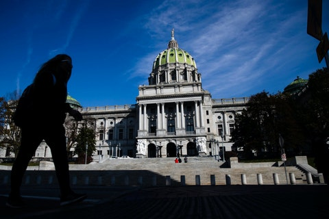 FILE- In this file photo from Nov. 19, 2019, a man is silhouetted in the shade as he walks by the Pennsylvania Capitol in Harrisburg, Pa. (AP Photo/Matt Rourke, File)