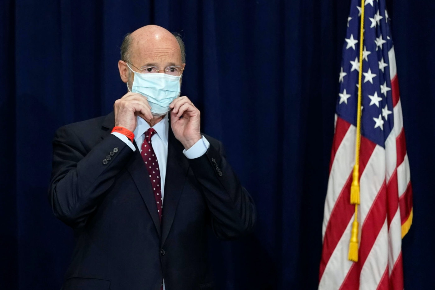 Pennsylvania Gov. Tom Wolf adjusts his face mask to protect against COVID-19 during a news conference in Harrisburg in November 2020. (AP File Photo/Julio Cortez)