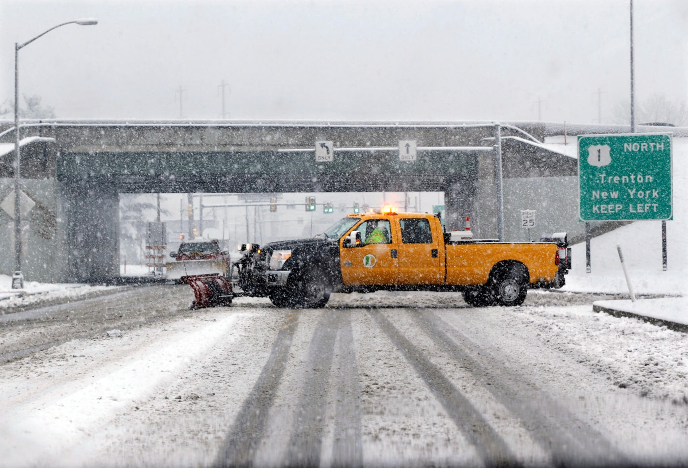 A snow plow drives across a road in a heavy snowfall in Morrisville, Pa., early Tuesday, Dec. 10, 2013. Much of Pennsylvania got socked Tuesday with another snowstorm that closed schools, delayed flights and made travel difficult through parts of the state. The governor's budget address was among the events postponed. (AP Photo/Mel Evans)