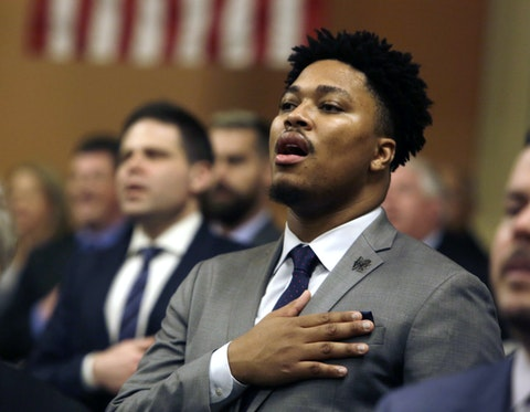 State representative Malcolm Kenyatta, a Black man, wears a gray suit and tie, and holds his right hand over his heart as he sings the National Anthem.