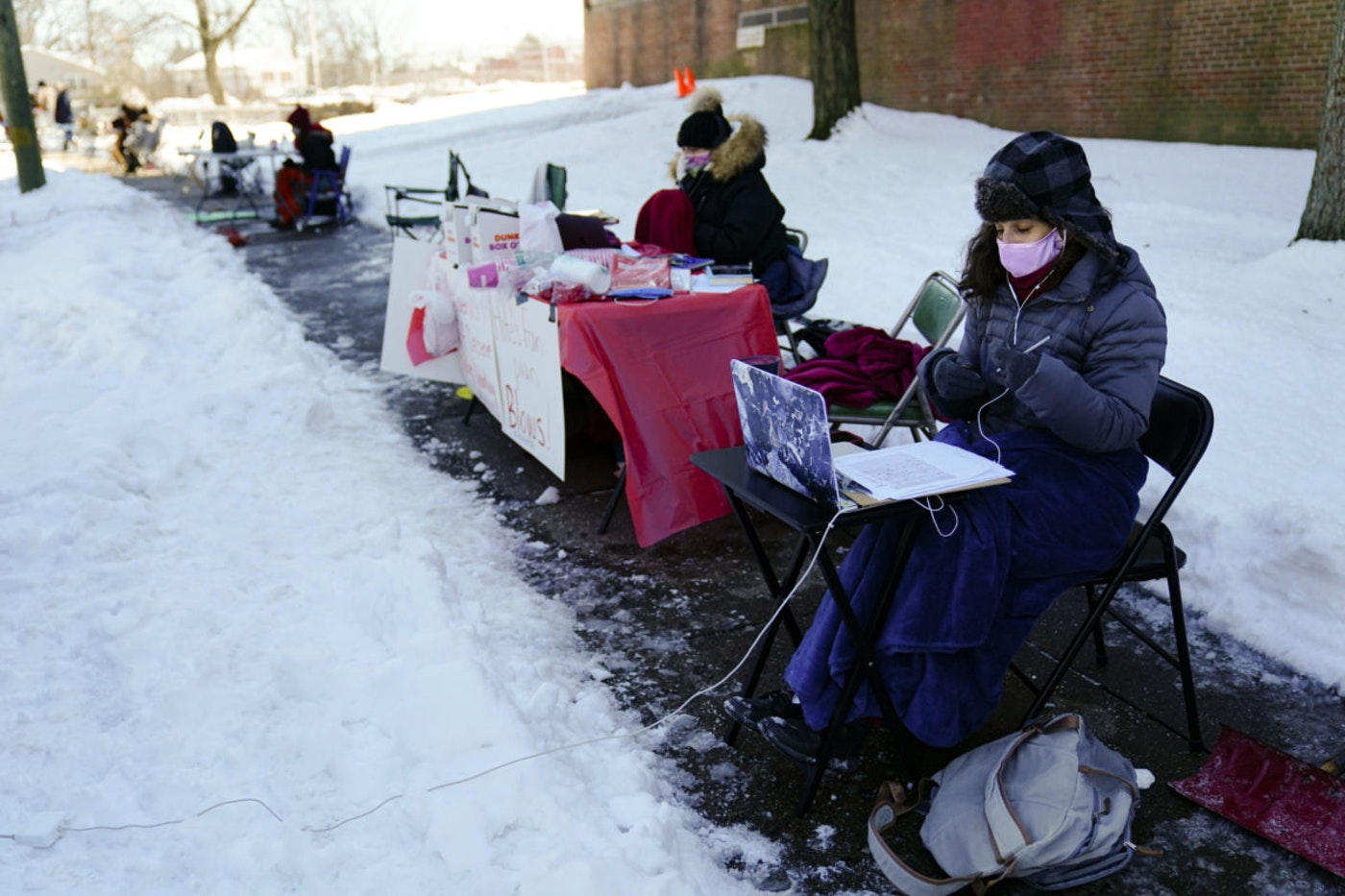 Teachers including Kathy Volin, right, and Dana Cohen, center, conduct their classes online from laptops during freezing temperatures outside the Joseph Greenberg School in Philadelphia, Monday, Feb. 8, 2021. A mediator will decide if Philadelphia school teachers must return to their classrooms despite safety concerns as the district plans to resume in-person instruction later this month. (AP Photo/Matt Rourke)