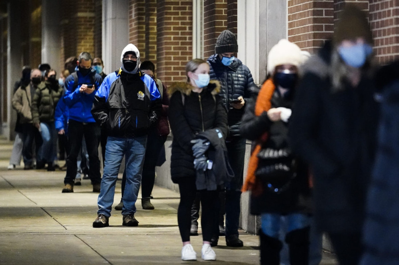 People wait in line at a COVID-19 vaccination site at the Pennsylvania Convention Center in Philadelphia, Wednesday, Feb. 3, 2021. The clinic opened to help provide second doses of COVID-19 vaccinations. (AP Photo/Matt Rourke)