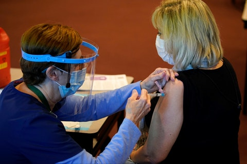 Pat Moore, left, with the Chester County, Pa., Health Department, administers the Moderna COVID-19 vaccine to Ann Yeager, a school district dental hygienist, at the Chester County Government Services Center, Dec. 29, 2020, in West Chester, Pa. (AP Photo/Matt Slocum)