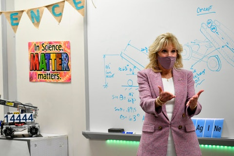 First lady Jill Biden stands in front of a white board in a robotics classroom. She is wearing a white dress, a dusky pink blazer, and a pink mask over her mouth and nose.