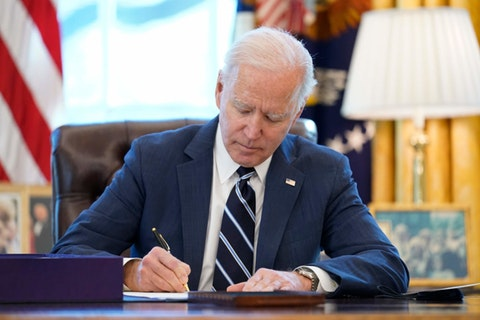President Joe Biden, wearing a navy blue suit white shirt, and navy blue tie, sits at a dark brown wooden desk as he signs the American Rescue Plan.