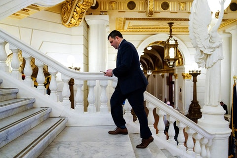 Rep. Mark Rozzi, D-Berks, checks his phone after speaking with members of the media at the Capitol in Harrisburg, Pa., Monday, March 22, 2021. Majority Republicans in the state Senate announced Monday they will not employ a rarely used emergency process to amend the Pennsylvania Constitution to give victims of child sexual abuse a two-year window in which to file civil lawsuits. (AP Photo/Matt Rourke)