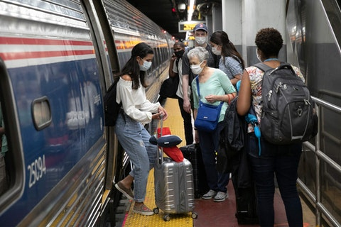 Travelers boarding a train at Amtrak's Penn Station, Aug. 6, 2020, in New York. If Congress moves and approves President Joe Biden's plan to increase Amtrak funding, folks at Penn Station could one day board a train to Scranton. (AP Photo/Mark Lennihan)