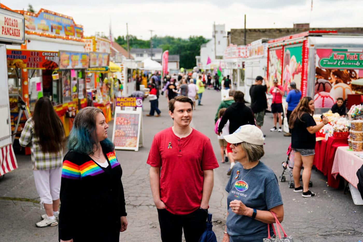 Alisha Hoffman-Mirilovich, left, Mark Shaffer, and Claudia Glennan visit with on another at the Edwardsville Pierogi Festival in Edwardsville, Pa., Friday, June 11, 2021. (AP Photo/Matt Rourke)