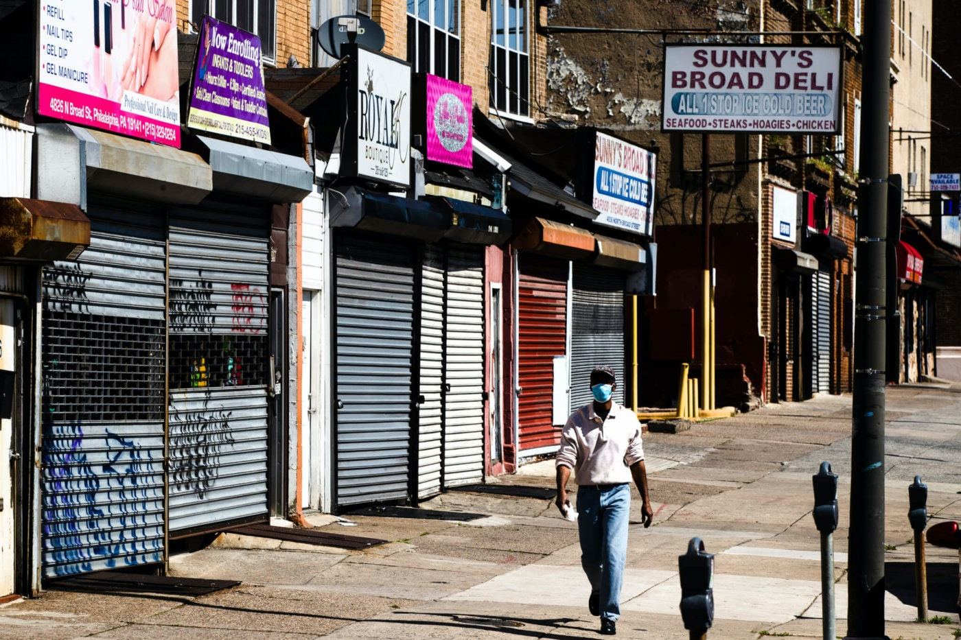 A person wearing a protective face mask as a precaution against the coronavirus walks past shuttered businesses in Philadelphia. (AP Photo/Matt Rourke)