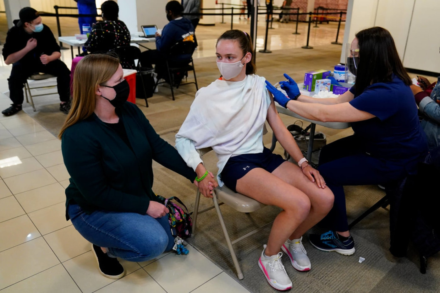 Meg Edwards, left, of Flourtown, Pa., comforts her daughter, Kate Edwards, 15, as she receives a Pfizer COVID-19 vaccination from registered nurse Philene Moore at a Montgomery County, Pa. Office of Public Health vaccination clinic at the King of Prussia Mall, Tuesday, May 11, 2021, in King of Prussia, Pa. (AP Photo/Matt Slocum)