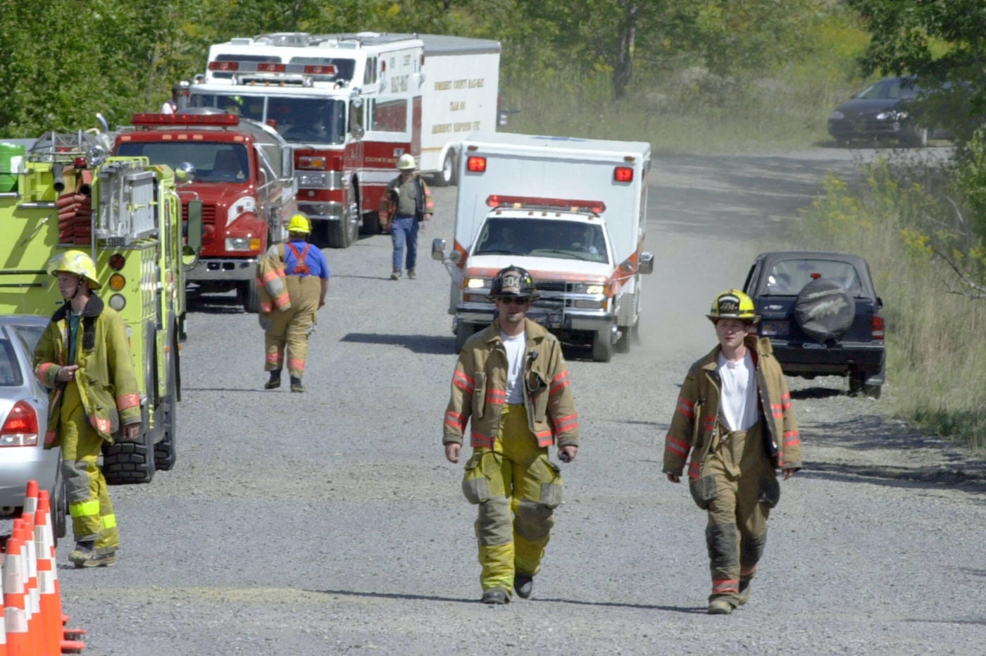 FILE - In this Tuesday, Sept. 11, 2001 file photo, an ambulance drives behind two firemen as they walk along the road near the crash scene of the United Airlines jet that crashed near Shanksville. (AP Photo/Keith Srakocic)