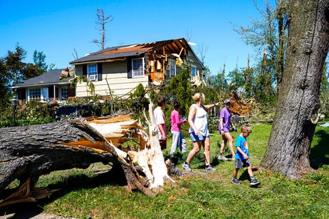 People walk by a downed tree in Fort Washington Thursday, Sept. 2, 2021 in the aftermath of downpours and high winds from the remnants of Hurricane Ida that hit the area. (AP Photo/Matt Rourke)