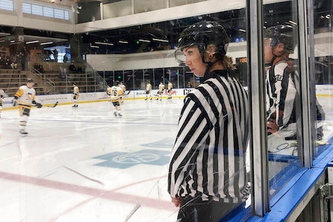 FILE - In this Sept. 6, 2019, file photo, linesman Kirsten Welsh watches at center ice as Pittsburgh Penguins and Boston Bruins players take the ice to prepare to play in the Sabres prospects hockey tournament in Buffalo, N.Y. Ten female officials will work games in the American Hockey League this season. Katie Guay, fellow referees Kelly Cooke, Jacqueline Zee Howard, Laura White, Samantha Hiller, Elizabeth Mantha and Amanda Tasson and linespeople Kendall Hanley, Welsh and Alexandra Clarke are part of 17 new AHL officials. (AP Photo/John Wawrow, File)