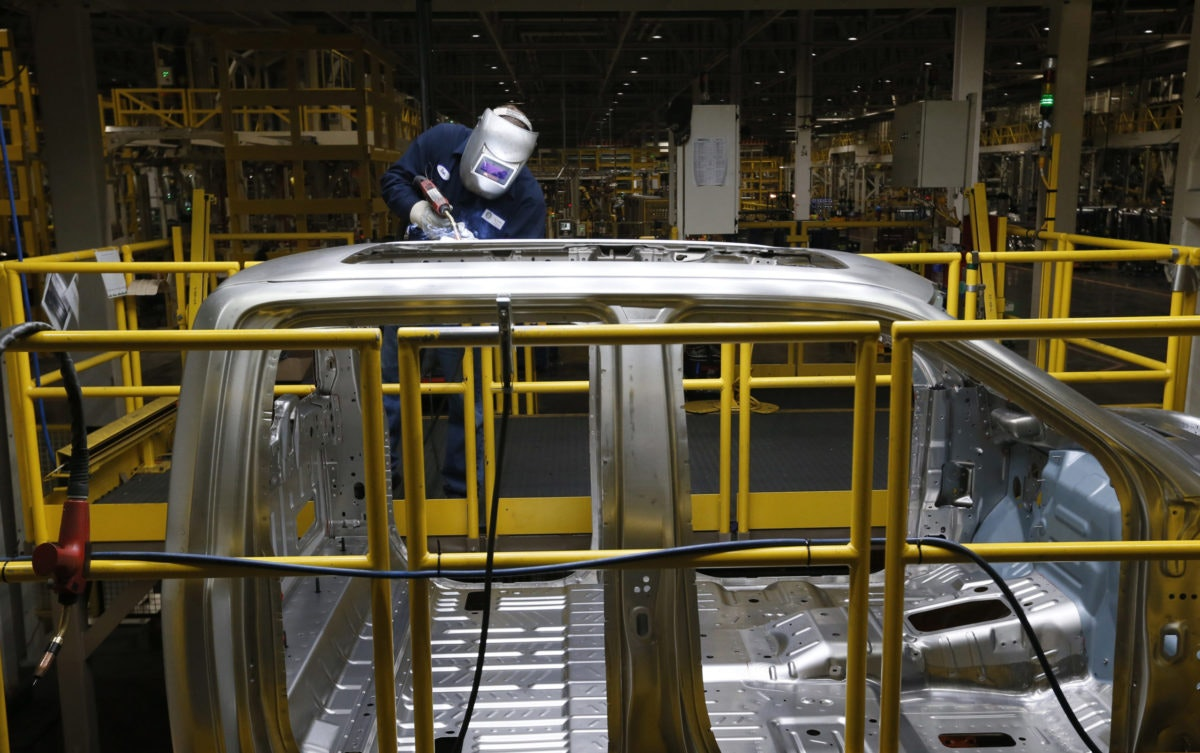 In this Nov. 11, 2014 photo, Ron Hudgins welds a 2015 Ford F-150 cab at the Dearborn Truck Plant in Dearborn, Mich. General Motors, Ford, jet engine maker Rolls-Royce and other companies are talking to their governments about repurposing idled factories to produce vital goods to fight the coronavirus such as ventilators and surgical masks. On Friday, March 20, 2020 President Donald Trump invoked the Korean War-era Defense Production Act, allowing the government to marshal the private sector to fight the COVID-19 pandemic. Although it allows the government to steer factories to overcome shortages, makers of heavy goods such as cars and trucks can't just flip a switch and produce something else. (AP Photo/Paul Sancya)