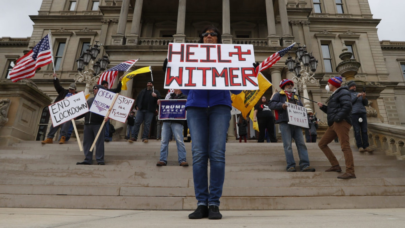 Dawn Perreca protests on the front steps of the Michigan State Capitol building in Lansing, Mich., Wednesday, April 15, 2020. Flag-waving, honking protesters drove past the Michigan Capitol on Wednesday to show their displeasure with Gov. Gretchen Whitmer's orders to keep people at home and businesses locked during the new coronavirus COVID-19 outbreak. (AP Photo/Paul Sancya)