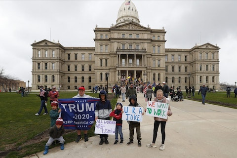 Children pose for a photograph during a protest at the State Capitol in Lansing, Mich., Wednesday, April 15, 2020. Flag-waving, honking protesters drove past the Michigan Capitol on Wednesday to show their displeasure with Gov. Gretchen Whitmer's orders to keep people at home and businesses locked during the new coronavirus COVID-19 outbreak. (AP Photo/Paul Sancya)
