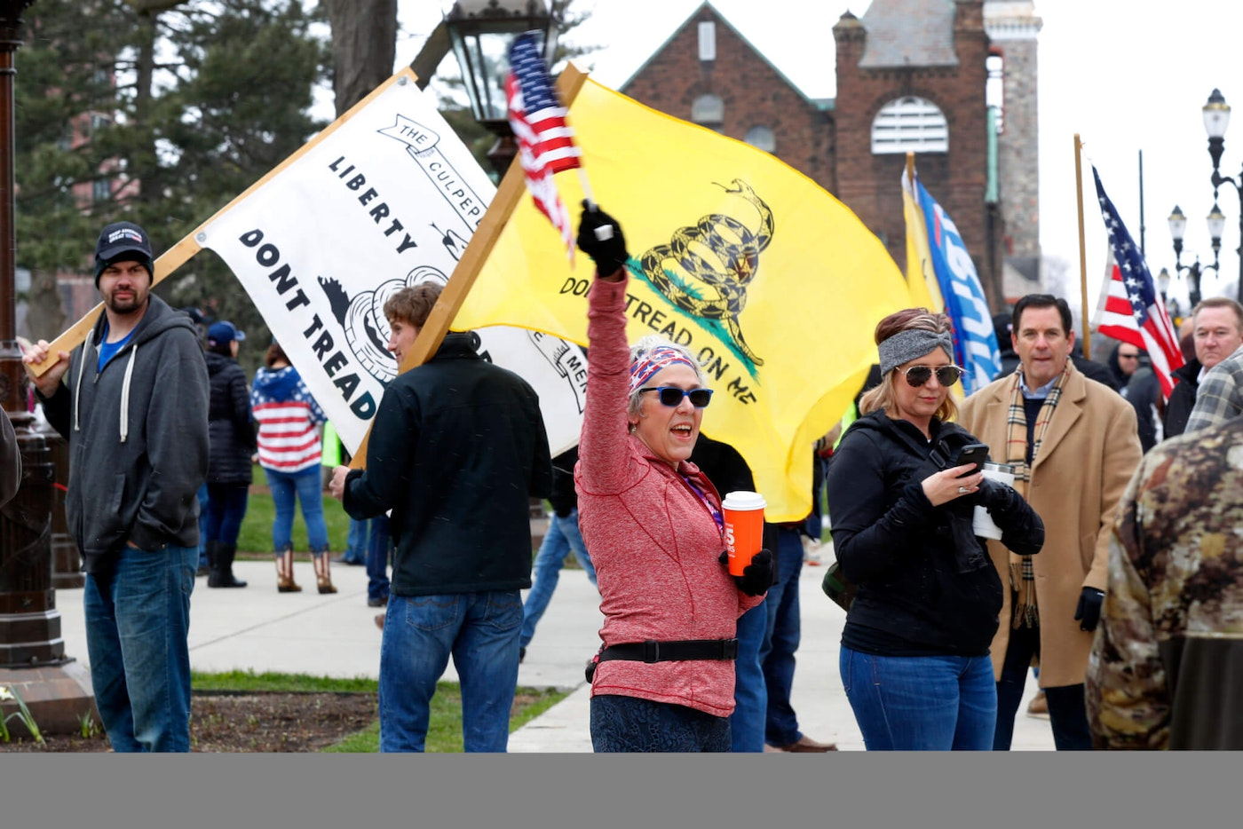 Protesters attend a rally outside the State Capitol in Lansing, Mich., Wednesday, April 15, 2020. Flag-waving, honking protesters drove past the Michigan Capitol on Wednesday to show their displeasure with Gov. Gretchen Whitmer's orders to keep people at home and businesses locked during the new coronavirus COVID-19 outbreak. (AP Photo/Paul Sancya)