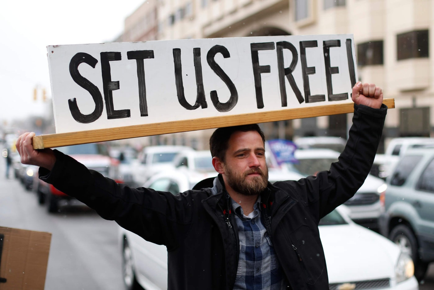 Steve Polet holds a sign during a protest at the State Capitol in Lansing, Mich., Wednesday, April 15, 2020. Flag-waving, honking protesters drove past the Michigan Capitol on Wednesday to show their displeasure with Michigan Gov. Gretchen Whitmer's orders to keep people at home and businesses locked during the new coronavirus COVID-19 outbreak. (AP Photo/Paul Sancya)