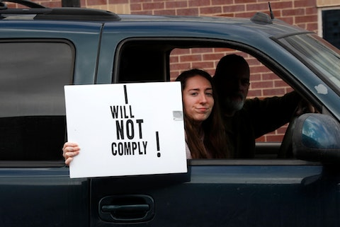 A passenger in a vehicle holds a sign during a protest at the State Capitol in Lansing, Mich., Wednesday, April 15, 2020. Flag-waving, honking protesters drove past the Michigan Capitol on Wednesday to show their displeasure with Gov. Gretchen Whitmer's orders to keep people at home and businesses locked during the new coronavirus COVID-19 outbreak. (AP Photo/Paul Sancya)