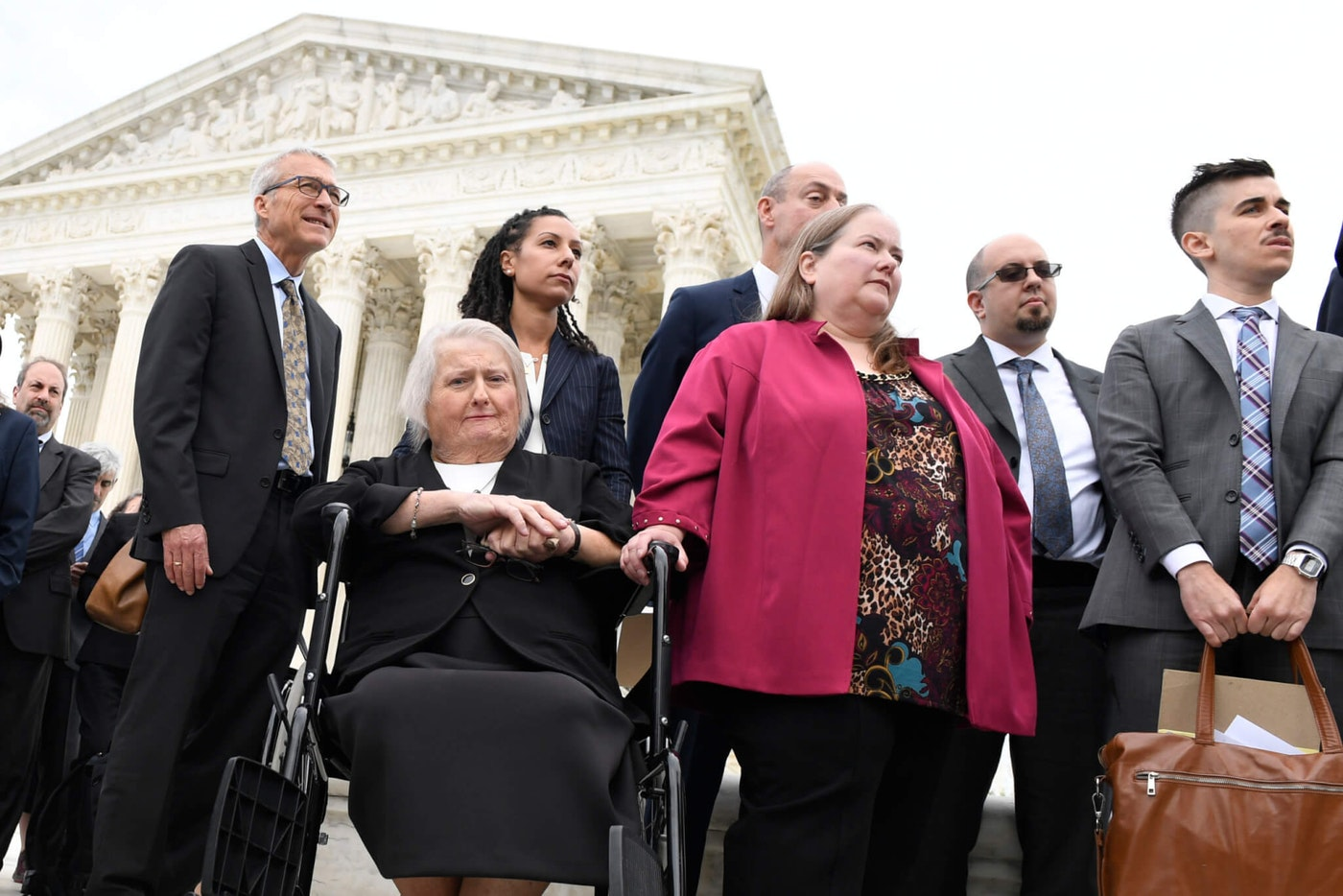 Aimee Stephens, seated, and her wife Donna Stephens, in pink, listen during a news conference outside the Supreme Court in Washington, Tuesday, Oct. 8, 2019. Aimee Stephens lost her job when she told Thomas Rost, owner of the Detroit-area R.G. and G.R. Harris Funeral Homes, that she had struggled with gender identity issues almost her whole life. Chase Strangio, listening at right, is an attorney with the American Civil Liberties Union who will be argues in the Harris Funeral Homes case on behalf of Aimee Stephens. (AP Photo/Susan Walsh)