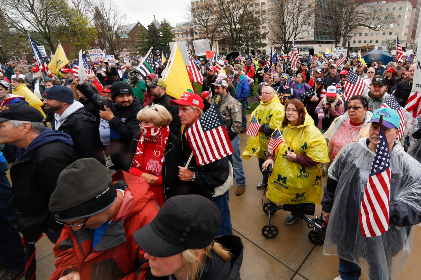 Protesters rally at the State Capitol in Lansing, Mich., Thursday, April 30, 2020. Hoisting American flags and handmade signs, protesters returned to the state Capitol to denounce Gov. Gretchen Whitmer's stay-home order and business restrictions due to COVID-19 while lawmakers met to consider extending her emergency declaration hours before it expires.. (AP Photo/Paul Sancya)