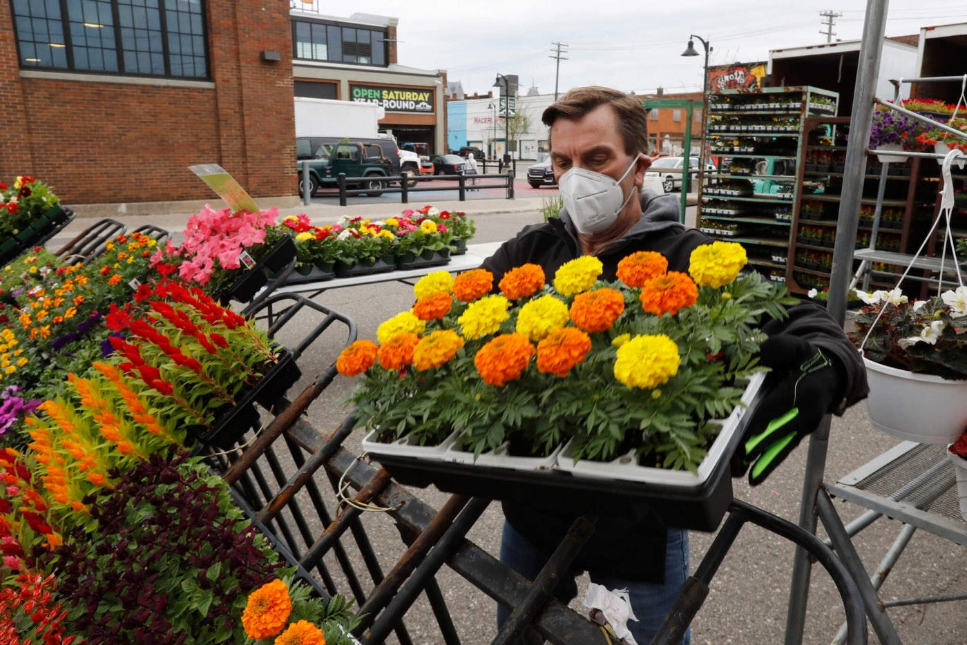 John Spens of Geier Farms sets up at the Detroit Farmers Market, Saturday, May 2, 2020, in Detroit. Farmers, growers and operators of open-air markets are heading into one of their busiest times of year while facing the added challenge of the coronavirus. Shoppers venturing to farmers markets this spring are likely to see a lot fewer vendors and fellow customers. The ones they do see will be taking precautions such as the wearing of face masks and frequent use of hand sanitizer. (AP Photo/Carlos Osorio)