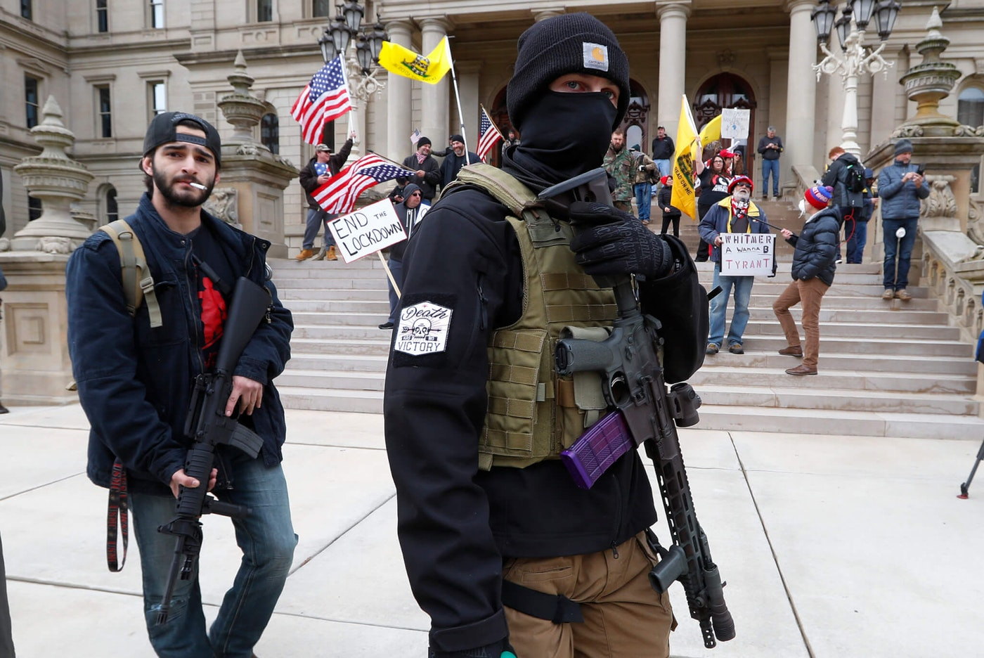 In this April 15, 2020 photo, protesters carry guns outside the Capitol Building in Lansing, Mich. Attorney General Dana Nessel said Friday, May 8, 2020, that a commission overseeing the state Capitol can legally ban guns from the building, contradicting panel leaders' contention that only the Legislature can do so. (AP Photo/Paul Sancya)