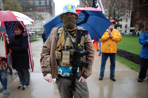 A protester carries his rifle during a rally against Michigan's coronavirus stay-at-home order at the State Capitol in Lansing, Mich., Thursday, May 14, 2020. (AP Photo/Paul Sancya)