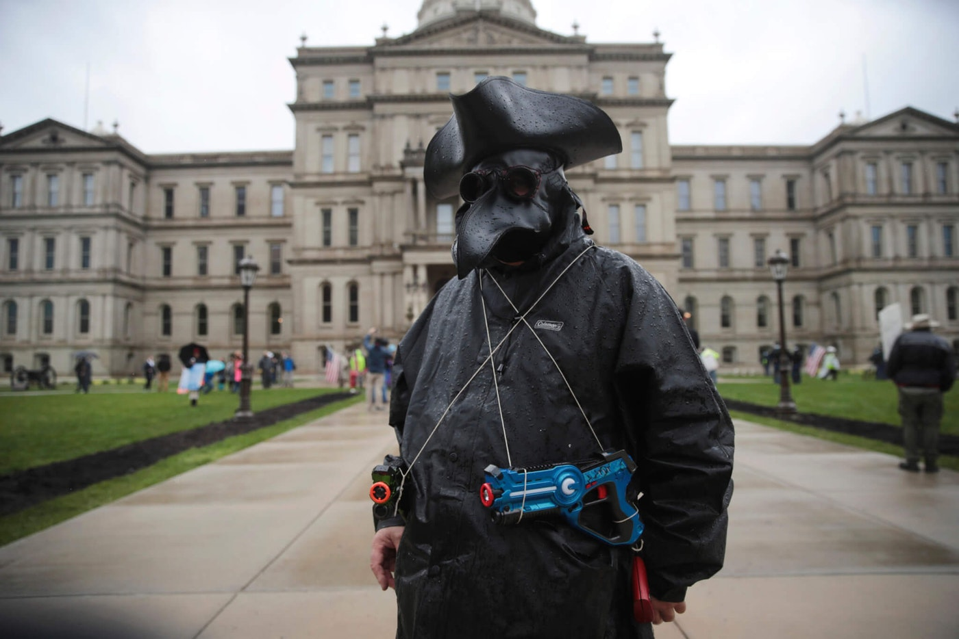 A protester with toy weapons watches during a rally against Michigan's coronavirus stay-at-home order at the State Capitol in Lansing, Mich., Thursday, May 14, 2020. (AP Photo/Paul Sancya)