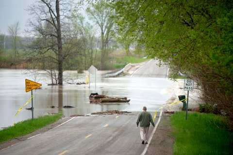 Freeland resident Cyndi Ballien walks up to get a closer look as heavy rain floods North Gleaner Road near its intersection with Tittabawassee Road on Tuesday, May 19, 2020, in Saginaw County, Mich. People living along two mid-Michigan lakes and parts of a river were evacuated Tuesday following several days of heavy rain that produced flooding and put pressure on dams in the area. (Jake May/The Flint Journal via AP)
