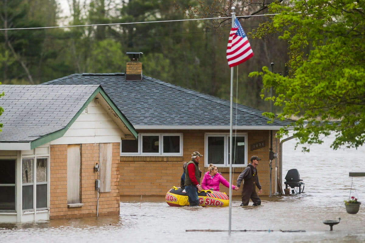 People help each other travel from one home to another using an inflatable raft on Oakridge Road on Wixom Lake, Tuesday, May 19, 2020 in Beaverton, Mich. People living along two mid-Michigan lakes and parts of a river have been evacuated following several days of heavy rain that produced flooding and put pressure on dams in the area. (Katy Kildee/Midland Daily News via AP)